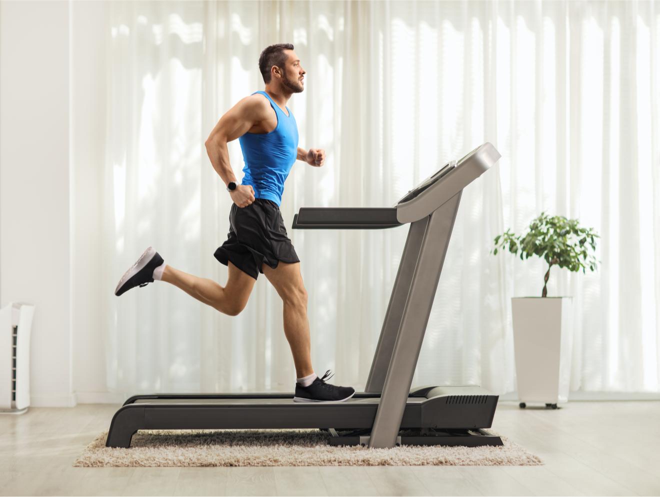 Un homme s'entraîne à la maison sur son tapis de course