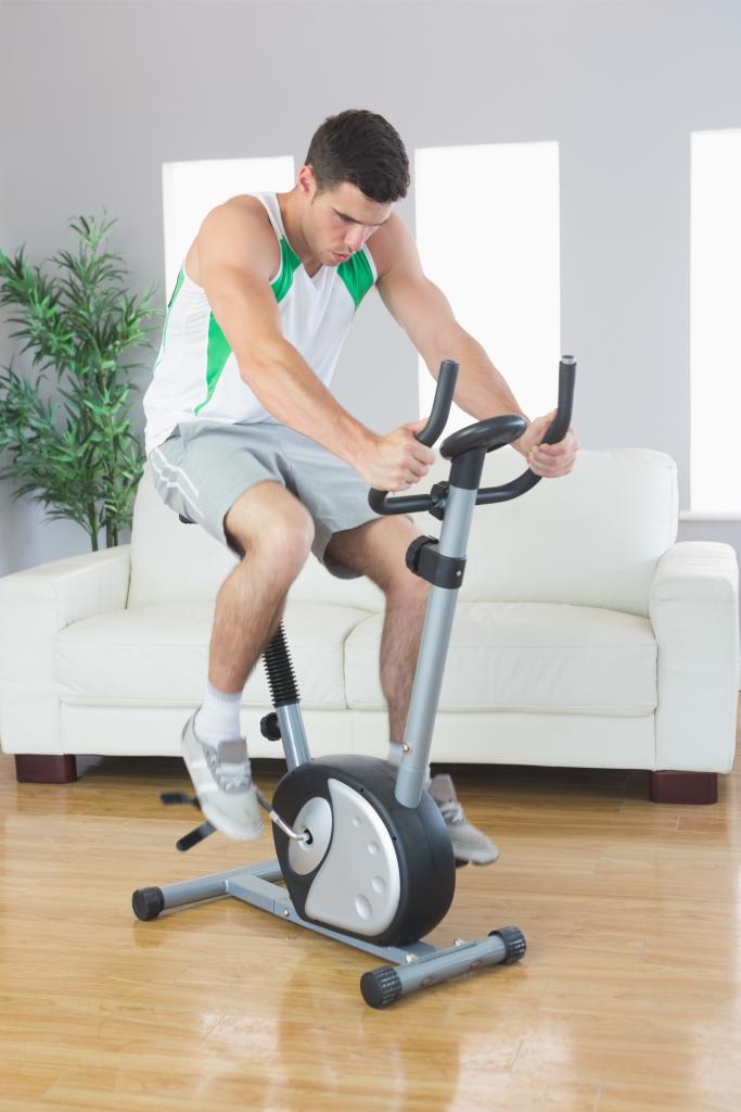 Un Homme S'entraine Sur Un Vélo D'appartement Dans Son Salon