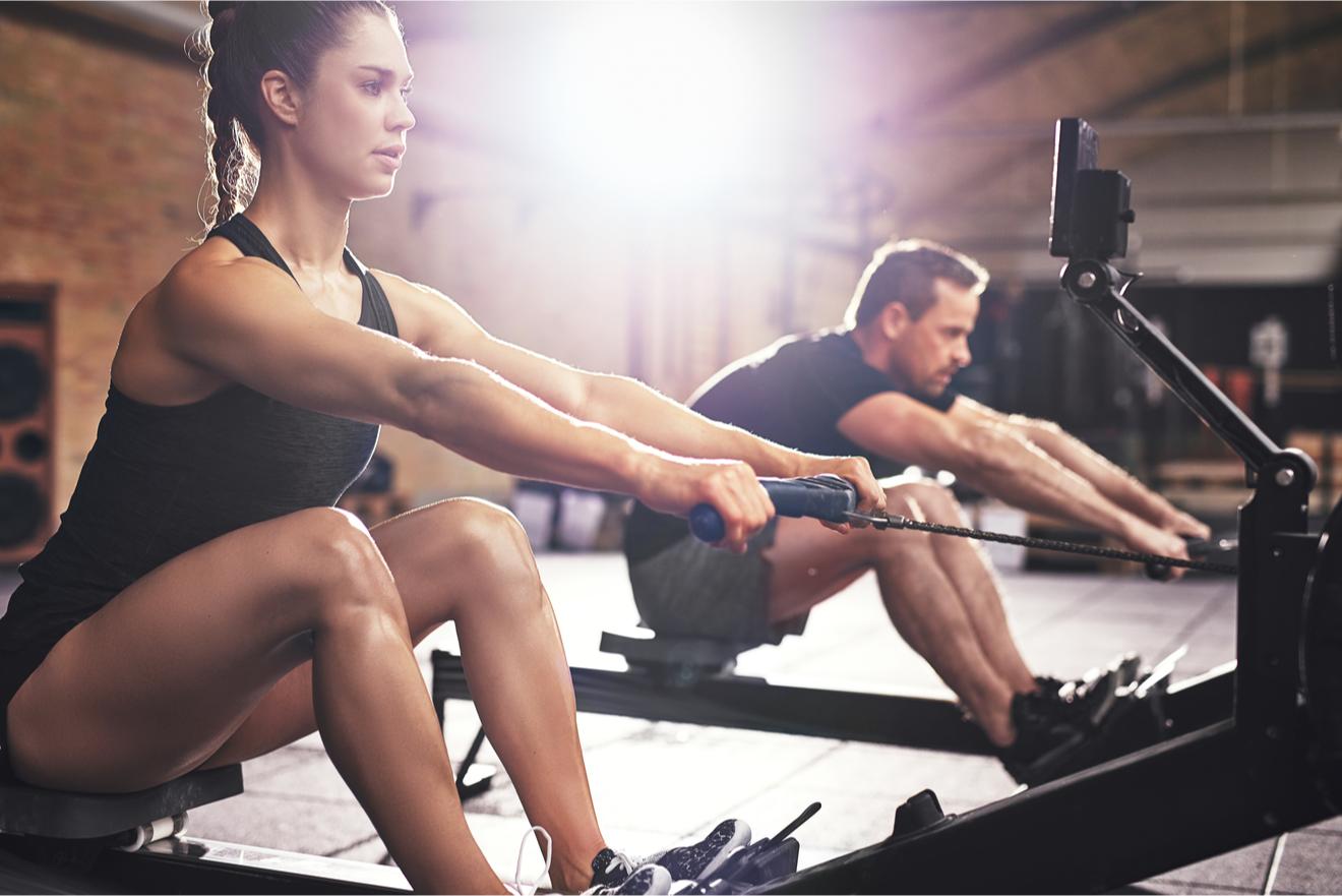 Une Femme Et Un Homme Font Du Rameur Dans Une Salle De Sport