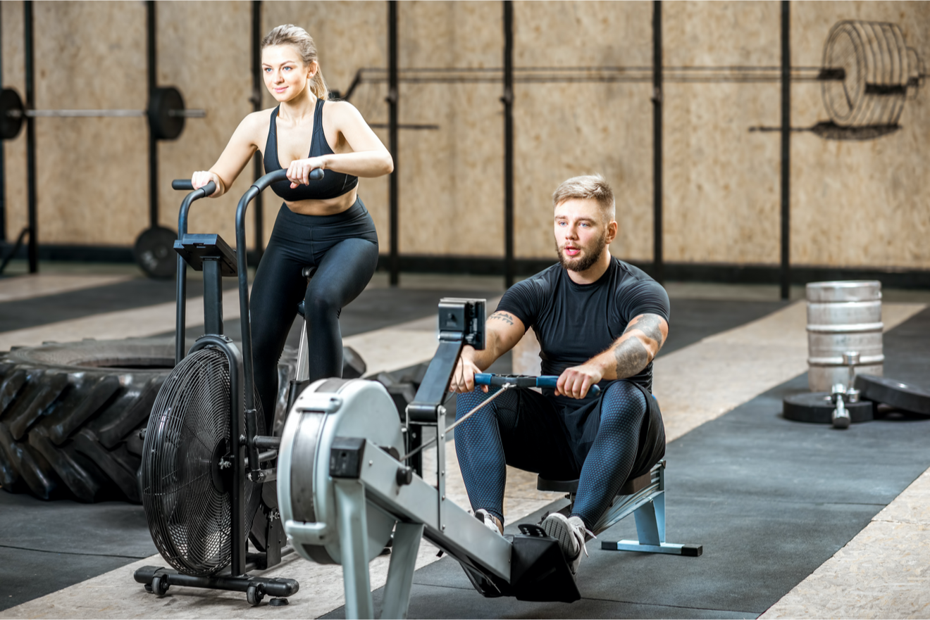 Une Femme Sur Un Vélo D'appartement Et Un Homme Sur Un Rameur à la salle de gym
