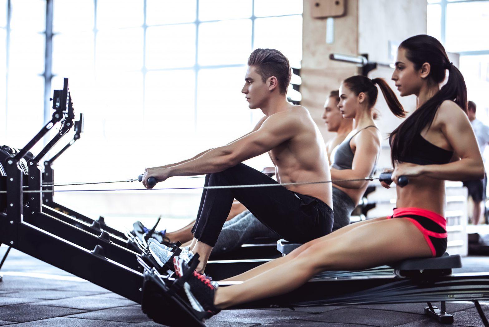 De jeunes gens s'entrainent sur des rameurs dans une salle de sport