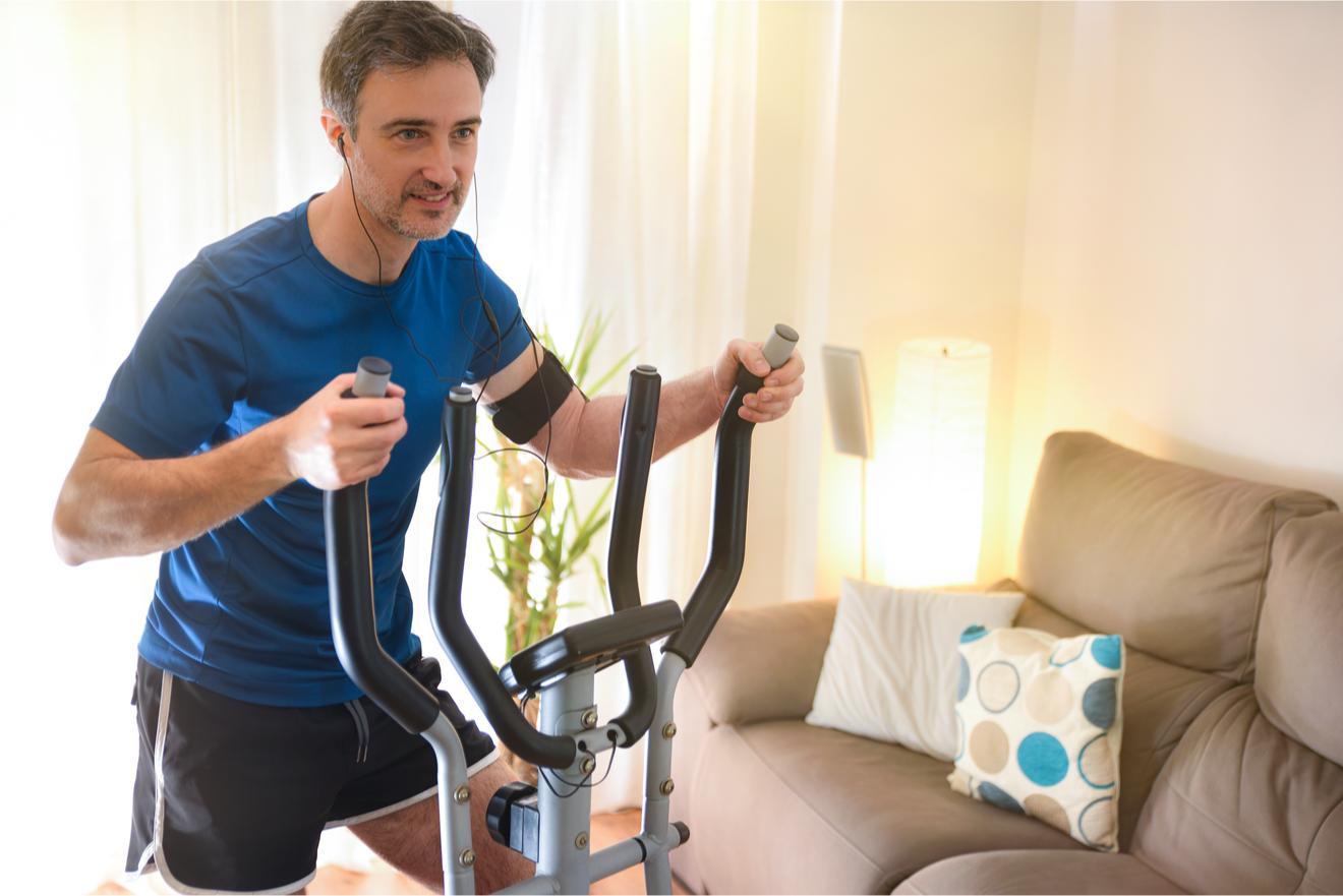Un Homme S'entraine Dans Son Salon Sur Un Vélo Elliptique pour perdre du ventre