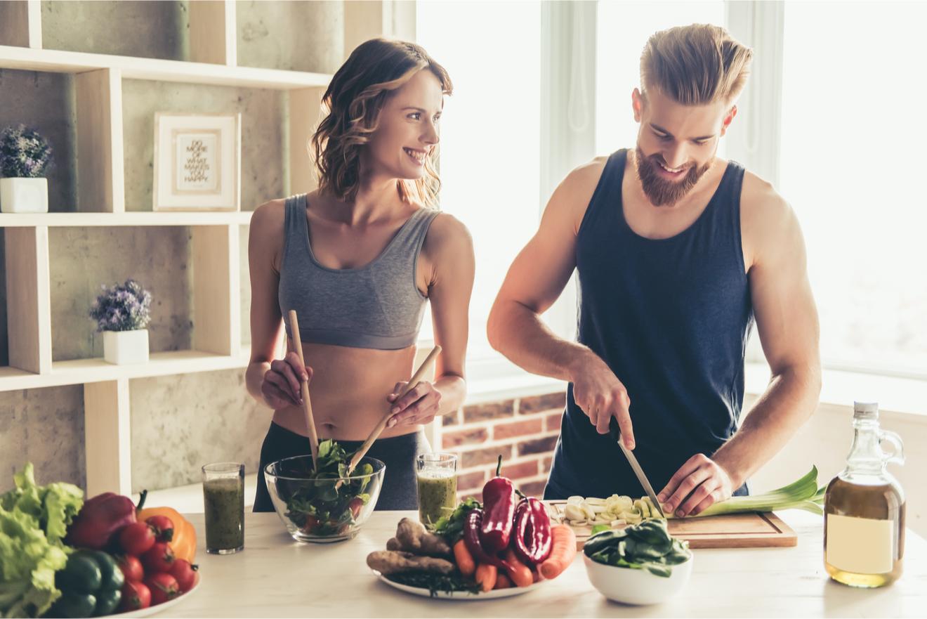 Couple De Sportifs Cuisinant Des Aliments Sains