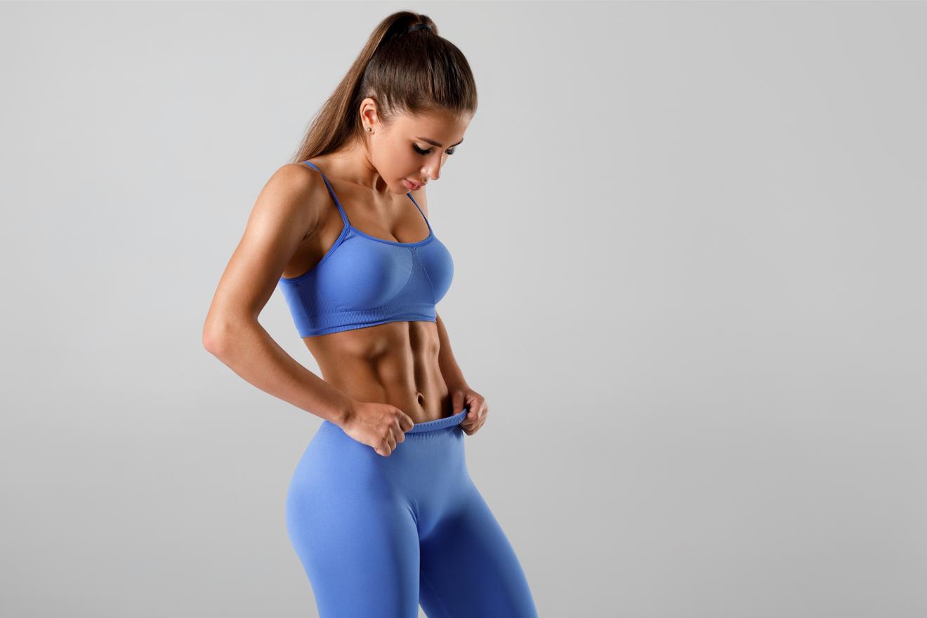 Une Jeune Femme Mince En Tenue De Sport Dévoile Ses Muscles Abdominaux