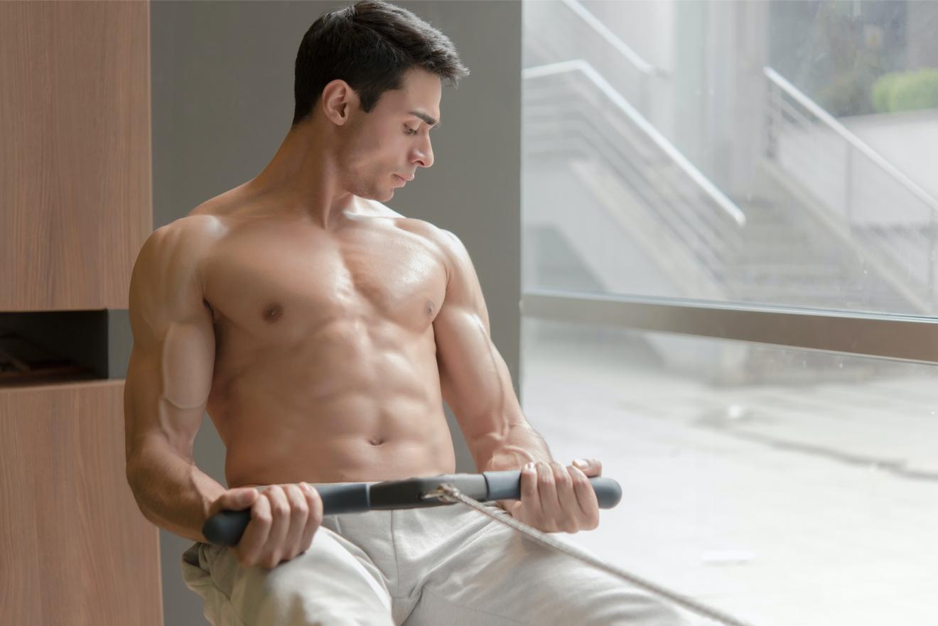Jeune Homme Se Muscle Sur Un Rameur