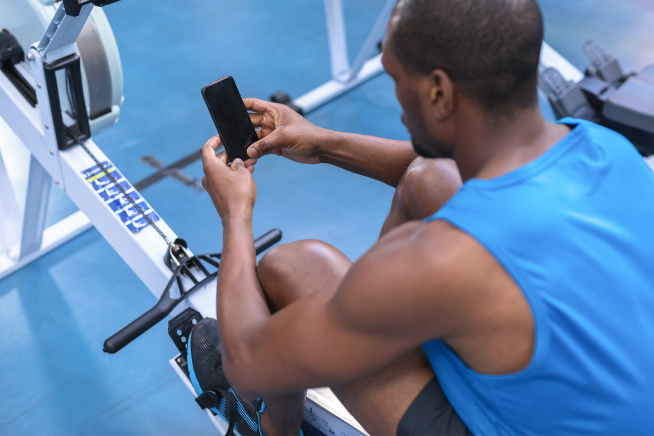 Un Homme Utilise Son Téléphone sur un rameur pour mesurer ses performances sportives