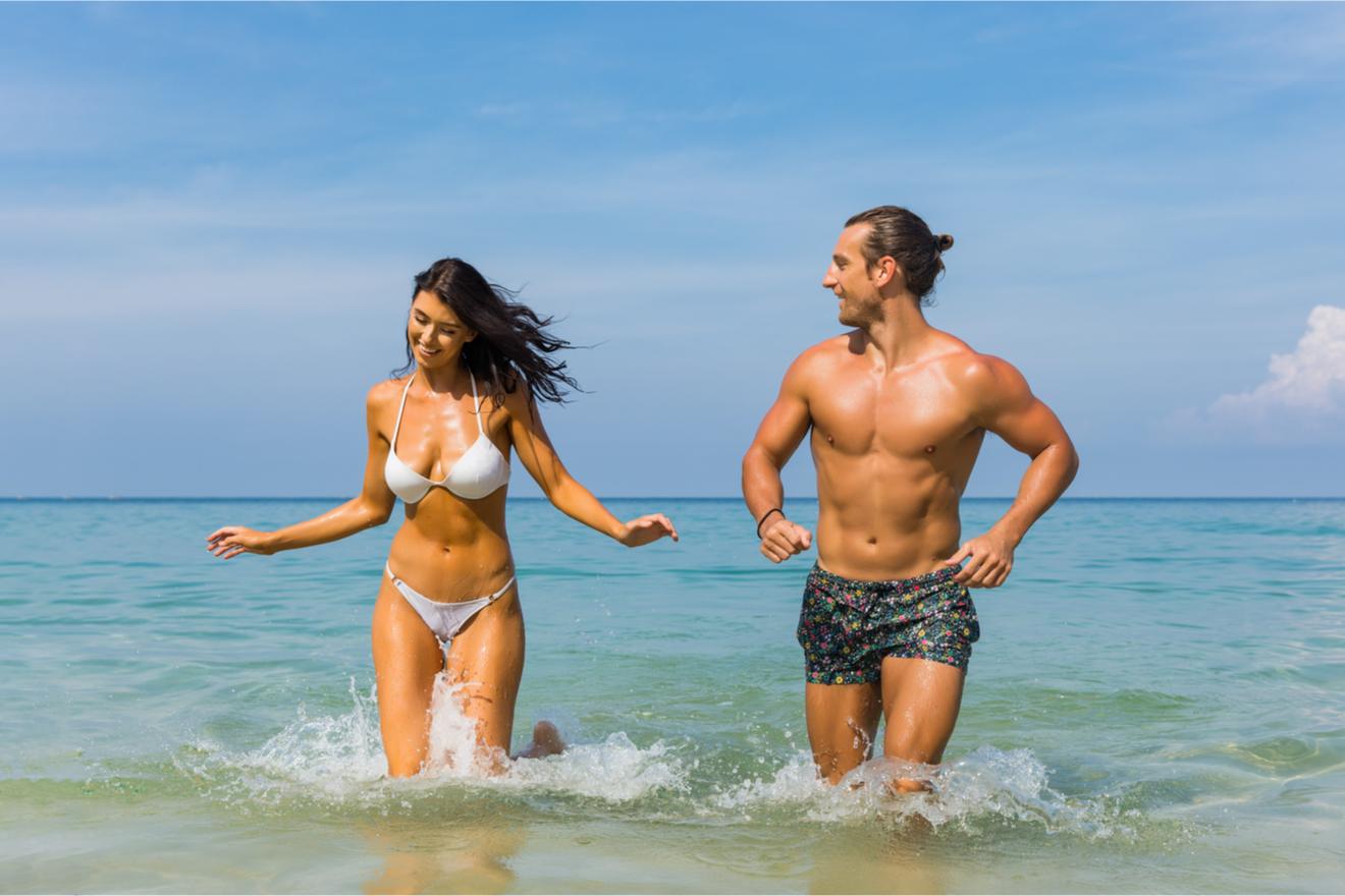 Un Couple De Sportifs à La Plage Exhibent Leur Beach Body