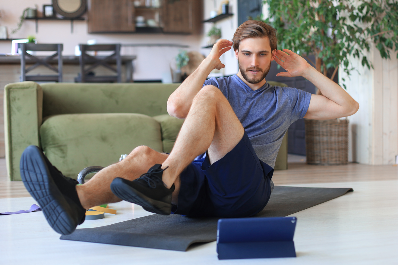Homme Faisant Exercices Abdos à La Maison En Suivant Cours Sur Sa Tablette