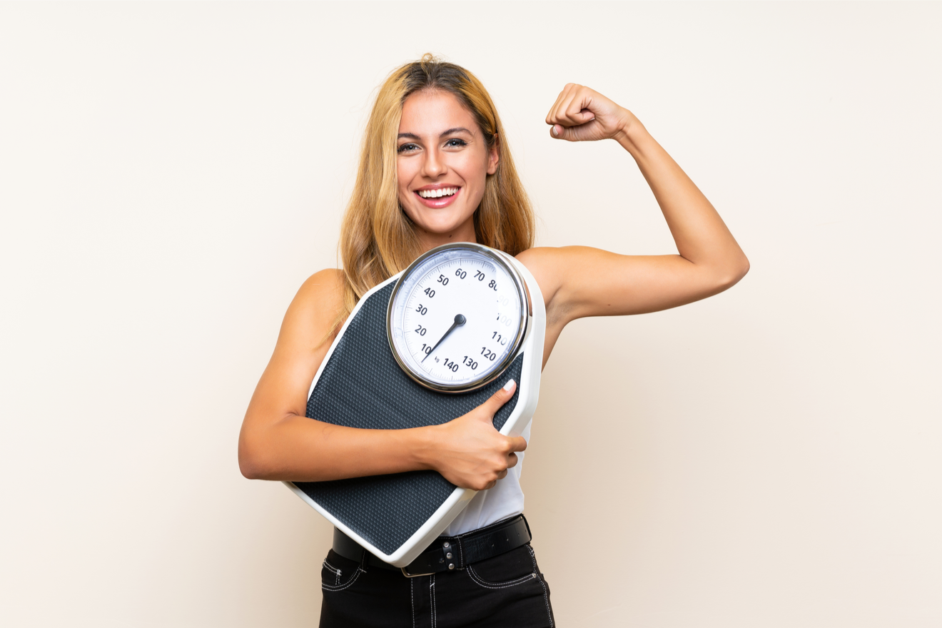 Une Femme Blonde Tient Une Balance Dans Une Main Et Montre Ses Biceps