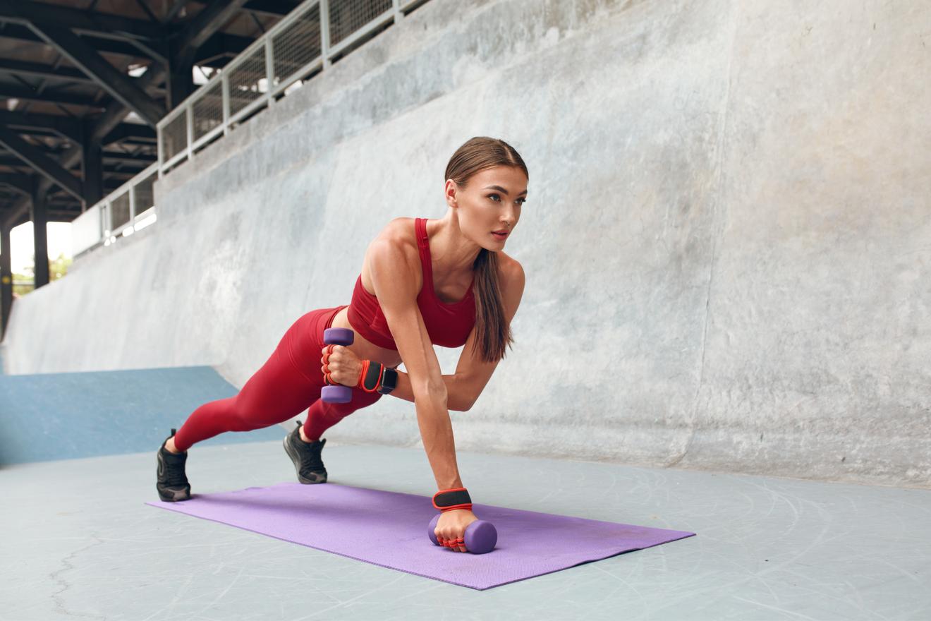 Une Femme Réalise Une Planche Avec Des Haltères Lors De Sa Séance De Musculation