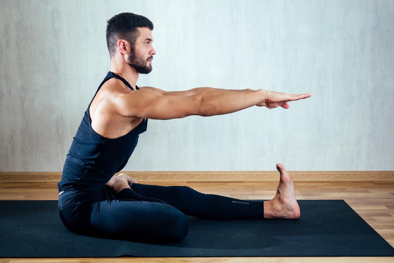 Un Homme Réalise Une Pose De Yoga Sur Un Tapis Noir